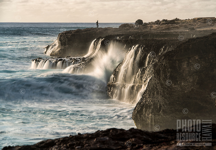 Waves crash off the rocky shore of Ka'ena Point State Park, O'ahu; a woman sets fishing lines in the background.