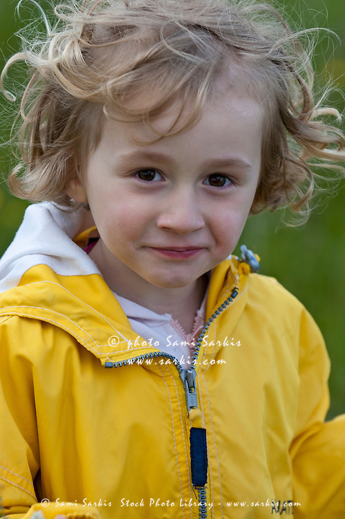Little girl wearing a yellow raincoat, Provence, France.