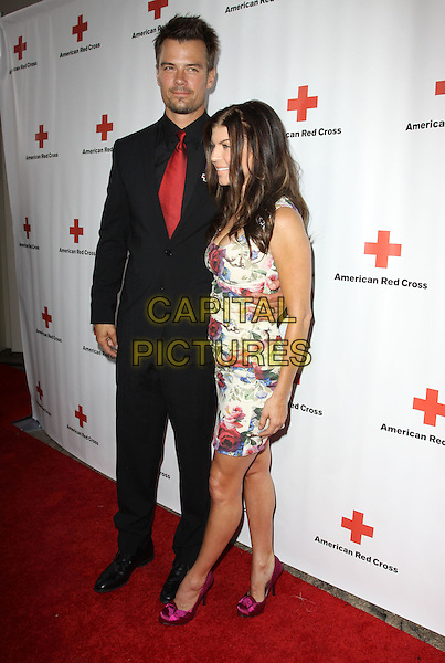 JOSH DUHAMEL & FERGIE (STACY FERGUSON).The American Red Cross Red Tie Affair Fundraiser Gala held At Fairmont Miramar Hotel, Santa Monica, California, USA, 17th April 2010..full length tall short  black suit red tie shirt couple husband wife married couple  rose floral white print cleavage side  pink purple shoes dress.CAP/ADM/KB.©Kevan Brooks/AdMedia/Capital Pictures.