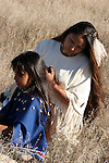 A Native American Indian Woman plays with the hair of a young girl outside in the prairie of South Dakota