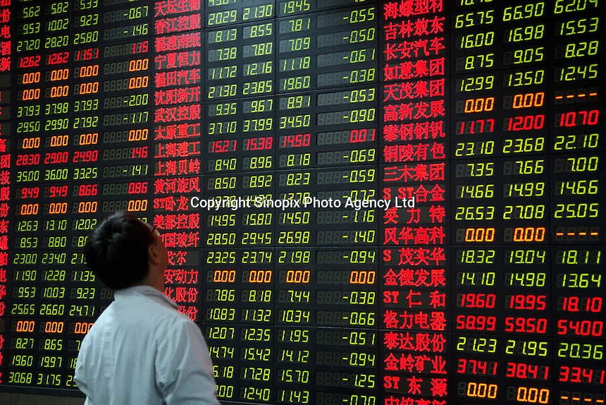 Investors look at a trading board showing overwhelmingly green numbers, which in China indicates a drop in stock price, at a securities exchange house in Shanghai, China. Investors are worried more government measures to slow inflation and tighten money supply will curb economic growth, as well as rising possibility that the United States, largest importer of Chinese goods, is slipping into a recession..22 Jan 2008