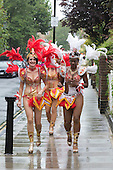 London, UK. 25 August 2014. Dancers from the Paraiso School of Samba get themselves ready for the Notting Hill Carnival parade on a wet Bank Holiday Monday. They were lucky as the heavy rain briefly stopped and they had some time to pose for photographers.