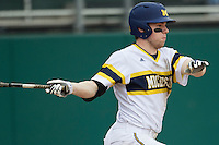 Michigan Wolverines shortstop Travis Maezes (9) follows through on his swing during the NCAA baseball game against the Washington Huskies on February 16, 2014 at Bobcat Ballpark in San Marcos, Texas. The game went eight innings, before travel curfew ended the contest in a 7-7 tie. (Andrew Woolley/Four Seam Images)