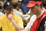 Two brothers, Eric and Robert Mizrachi sit next to each other at a table.