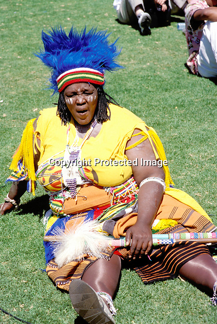 CUZULUS02050.Culture. Zulus. South Africa. Johannesburg. Participants at a Zulu rally. Woman wearing colourful clothes sitting on grass..©Per-Anders Petterson/iAfrika Photos.