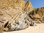 Folded sedimentary rock strata dipping downwards in cliff at Praia dos Alteirinhos, Zambujeira do Mar, Parque Natural do Sudoeste Alentejano e Costa Vicentina, Costa Vicentina and south west Alentejo natural park, Zambujeira do Mar, Alentejo Littoral, Portugal, southern Europe