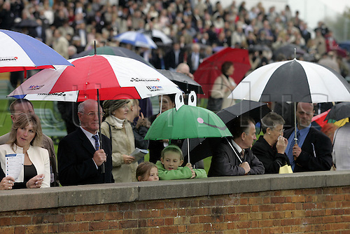 25 September 2004: Racegoers shelter under umbrellas in the members enclosure at Ascot during the Finale Meeting. Photo: Neil Tingle/Action Plus...040925 horse racing crowd crowds