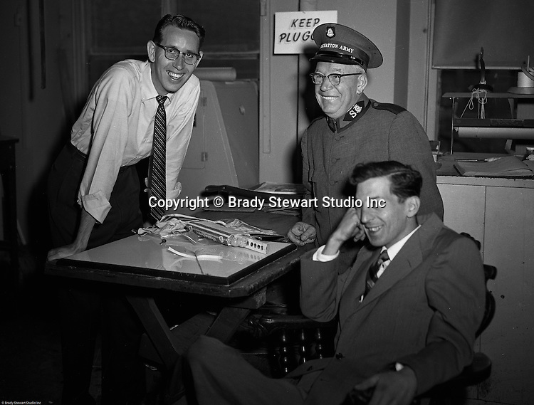 Pittsburgh PA:  Major Henry Dries from the Salvation Army at Brady Stewart Studio of a PR shot - 1955.  Major Dries  with Brady Stewart Photographers Dave VanDeVeer and Ross Catanza. <br /> Major Dries directed Public Relations and Disaster Services for the Salvation Army in Pittsburgh.  In the 1960's he was promoted to Brigadier due to his exceptional job performance and standing in the community.  He was a frequent visitor to the studio due to friendship with Brady Stewart Sr.
