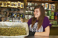 USA. Colorado state. Denver. A cheerful employee at Medicine Man is showing cannabis buds while standing behind the counter in the recreational section. Medicine Man began nearly six years ago as a small medical marijuana operation and has since grown to be the largest single marijuana dispensary, both recreational and medical, in the state of Colorado and has aspirations of becoming a national brand if pot legalization continues its march. Cannabis, commonly known as marijuana, is a preparation of the Cannabis plant intended for use as a psychoactive drug and as medicine. Pharmacologically, the principal psychoactive constituent of cannabis is tetrahydrocannabinol (THC); it is one of 483 known compounds in the plant, including at least 84 other cannabinoids, such as cannabidiol (CBD), cannabinol (CBN), tetrahydrocannabivarin (THCV), and cannabigerol (CBG). 19.12.2014 © 2014 Didier Ruef