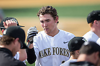 Keegan Maronpot (13) of the Wake Forest Demon Deacons is congratulated by teammates after scoring a run against the Miami Hurricanes at Wake Forest Baseball Park on March 21, 2015 in Winston-Salem, North Carolina.  The Hurricanes defeated the Demon Deacons 12-7.  (Brian Westerholt/Four Seam Images)