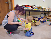 NWA Democrat-Gazette/BEN GOFF -- 05/23/15 Chelsea Nicholas of Springdale helps her son Luke Ryan, 1, pick out a book while shopping at the rummage sale at Good Shepherd Lutheran Church in Fayetteville on Saturday May 23, 2015. The sale, which will continue Saturday May 30 from 8:00a.m. to 3:00p.m., helps support the church's youth programs.