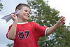 Boy flying a paper Airplane,