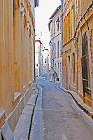 A man carrying a brief case walking on a winding street in the old town in Avignon, Vaucluse, Rhone, Provence, France