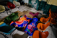 Patients' family members sleep on the floor in a patio inside the emergency department of a public hospital in San Salvador, El Salvador, 16 December 2015.