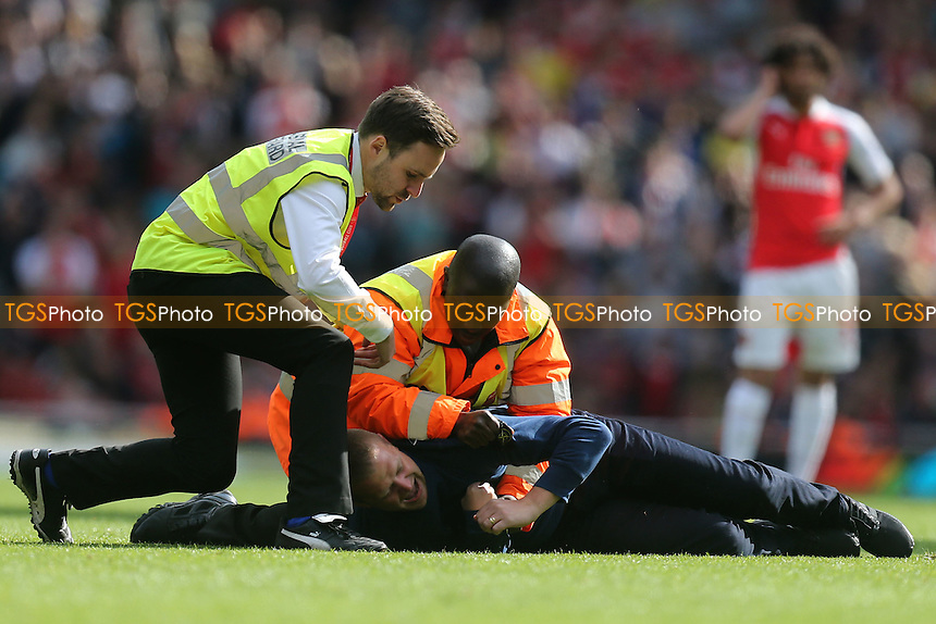 A pitch invader is stopped by the stewards during Arsenal vs Aston Villa, Barclays Premier League Football at the Emirates Stadium on 15th May 2016