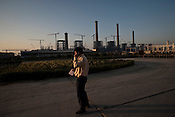 A Chinese engineer from Sepco speaks on the phone at the construction site of the Adani Power plant of 4620 MW capacity in Mundra port industrial city of Gujarat, India. Indian power companies have handed out dozens of major contracts to Chinese firms since 2008. Adani Power Ltd have built elaborate Chinatowns to accommodate Chinese workers, complete with Chinese chefs, ping pong tables and Chinese television. Chinese companies now supply equipment for about 25% of the 80,000 megawatts in new capacity.
