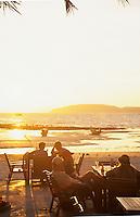 Golden sunset on travelers enjoying drinks at beach-side cafe, West hat Railay Rei Lei Beach, Thailand