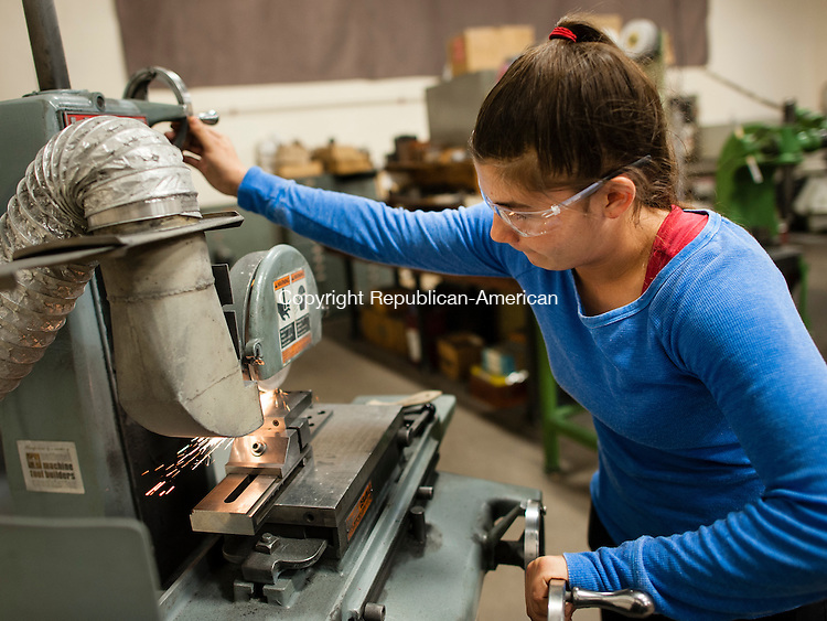 CHESHIRE, CT-30 April 2014-043014EC08-  Hannah Lenoce grinds steel at Marion Manufacturing in Cheshire. The 19-year-old has signed up to be an apprentice Tool-and-Die maker at the plant. The four year program is part of a state Labor Department-sponsored apprenticeship. Lenoce is the only female toolmaker at the plant and one of the youngest on staff. Erin Covey Republican-American