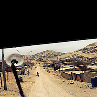 A sprawling settlement of houses, cut by an unpaved road, is seen on the dusty hillsides of Pachacútec, a desert shantytown in Lima, Peru, 20 January 2015.