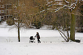 A mother with pushchair walks in the snow on Hampstead Heath, London.