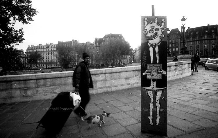 """10.2009 <br /> <br /> Homeless walking with his dog behind a poster where it is written """"support rich people"""".<br /> <br /> Sans abris marchant avec son chien derrière une affiche ou il est ecrit """"soutenez les riches""""."""