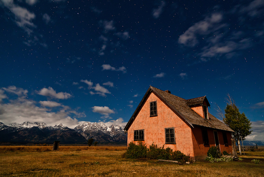 An empty pink house sits among a field of stars in Mormon Row within Grand Teton National Park.