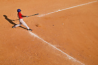 A boy hits a baseball during  a baseball game