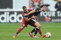 Washington, D.C.- March 29, 2014. Perry Kitchen (23) of D.C. United goes against Quincy Amarikwa of the Chicago Fire.  The Chicago Fire tied D.C. United 2-2 during a Major League Soccer Match for the 2014 season at RFK Stadium.