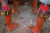 Bacaja village, Amazon, Brazil. Young men's legs decorated and painted with Urucum, in the men's hut; Xicrin tribe.