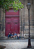 France, Paris, Four young men sitting on stairs and smoking outdoors in Le Marais
