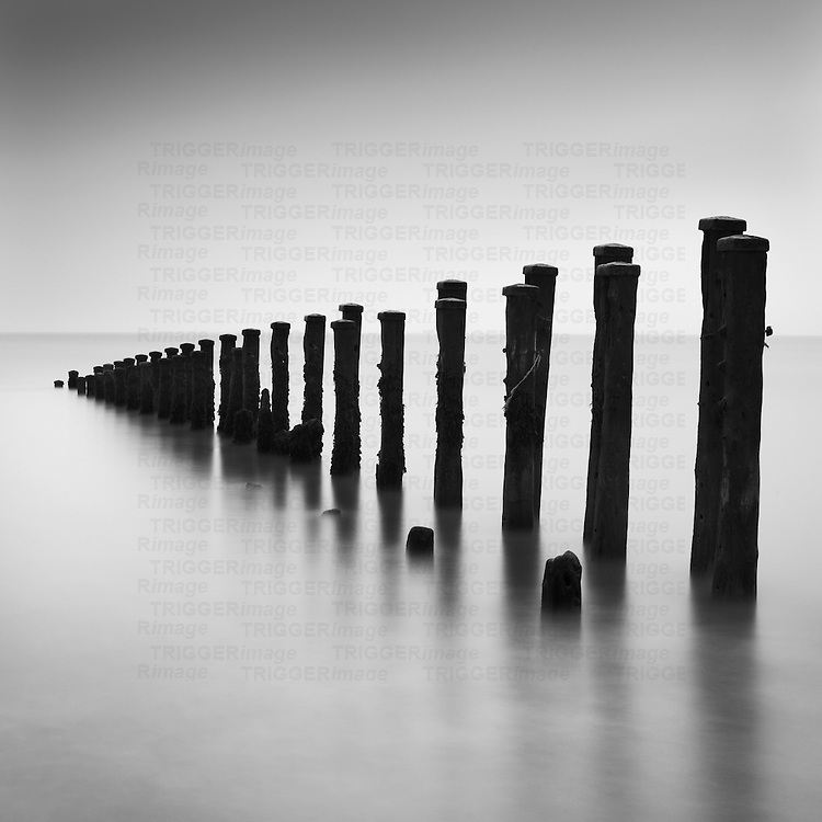 Wooden upright groynes or water breakers in the sea with long exposure