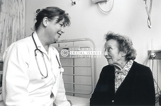 Elderly woman talking to female doctor on hospital ward,