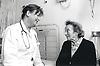 Elderly woman talking to female doctor on hospital ward,