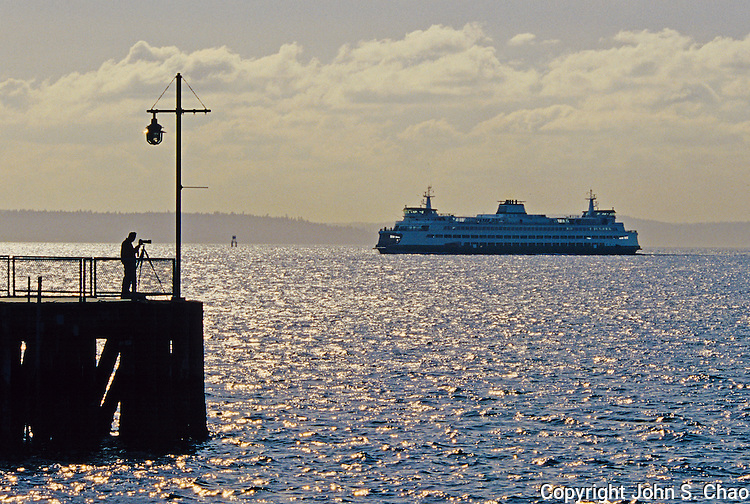 Silhouetted on a pier, a photographer views a passing Washington State Ferry in Elliott Bay, Puget Sound, Seattle, Washington State.
