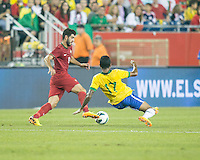Brazil midfielder Luiz Gustavo (17) attempts to tackle Portugal forward Nelson Oliveira (9).  In an International friendly match Brazil defeated Portugal, 3-1, at Gillette Stadium on Sep 10, 2013.