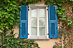 Window of house with blue shudders, lace curtains, and plants in Mandello del Lario, a town on Lake Como, Italy