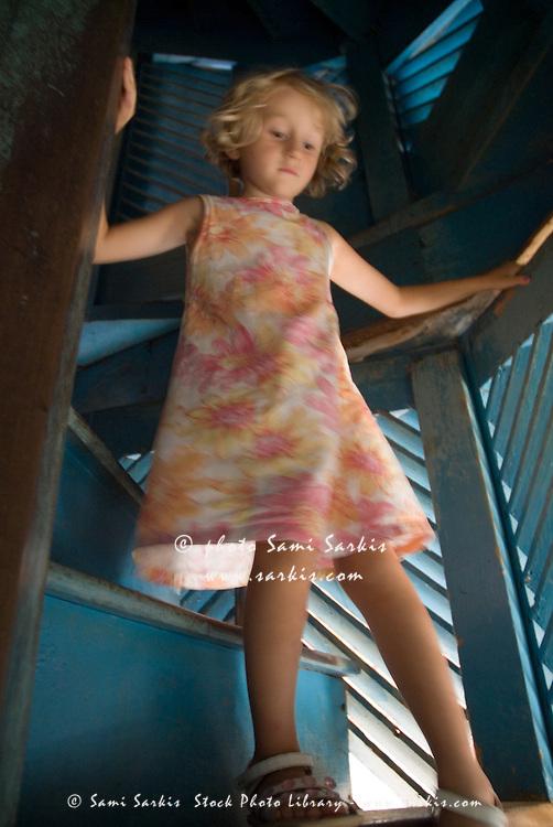 Little blond girl climbing down a spiral staircase, Trinidad, Cuba.