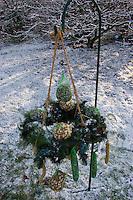Adventskranz im winterlichen Garten mit Vogelfutter, Vogel-Futter, Meisenknödeln, Nußsäckchen, Hirsestangen