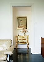 A gilded two-drawer chest is framed by an open doorway leading from the living room