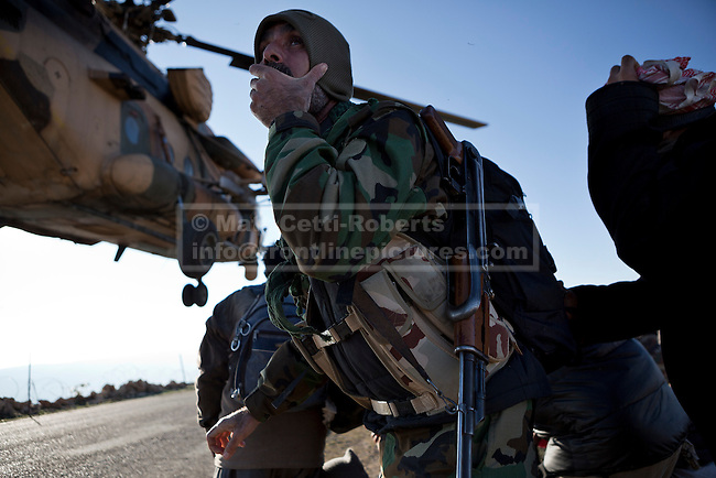 11/12/2014. Sinjar Mountains, Iraq. A Yazidi fighter holds his hat on to keep it from blowing off in the downdraft created by an Iraqi Air Force Mi-171E Hip helicopter during a mission to drop supplies and evacuate families on the top of Mount Sinjar.<br /> <br /> Although a well publicised exodus of Yazidi refugees took place from Mount Sinjar in August 2014 many still remain on top of the 75 km long ridge-line, with estimates varying from 2000-8000 people, after a corridor kept open by Syrian-Kurdish YPG fighters collapsed during an Islamic State offensive. The mountain is now surrounded on all sides with winter closing in, the only chance of escape or supply being by Iraqi Air Force helicopters.