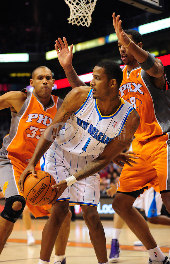 Dec. 26, 2011; Phoenix, AZ, USA; New Orleans Hornets guard/forward Trevor Ariza (center) controls the ball under pressure from Phoenix Suns guard Grant Hill (left) and center Channing Frye at the US Airways Center. The Hornets defeated the Suns 85-84. Mandatory Credit: Mark J. Rebilas-USA TODAY Sports