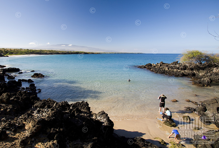 Family getting ready to go snorkeling at Hapuna Beach on the Big Island of Hawaii
