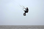 A competitor makes the most of the windy condidtions and gets some airtime during Round one of the British Kite Surfing Championships in Swansea Bay this afternoon, with the Mumbles lighthouse in the distance..