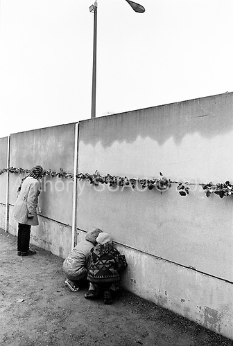 Berlin, Germany<br /> November 9, 2009<br /> <br /> Young and old a like visit the Wall Museum at a place the wall once stood and place flowers in the wall cracks and light candles on the 20th anniversary of the Fall of the Berlin wall.