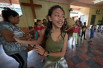 A girl dances with other children as they participate in a group activity in the office of Caritas in Manaus, Brazil. The weekly gathering is part of an educational and cultural program to combat sexual abuse and exploitation among at-risk children sponsored by the Catholic Church's social ministry.