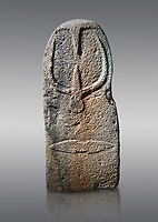 Late European Neolithic prehistoric Menhir standing stone with carvings on its face side. The representation of a stylalised male figure starts at the top with a long nose from which 2 eyebrows arch around the top of the stone. below this is a carving of a falling figure with head at the bottom and 2 curved arms encircling a body above. at the bottom is a carving of a dagger running horizontally across the menhir. Excavated from Bau Carradore II, Laconi. Menhir Museum, Museo della Statuaria Prehistorica in Sardegna, Museum of Prehoistoric Sardinian Statues, Palazzo Aymerich, Laconi, Sardinia, Italy. Grey background.