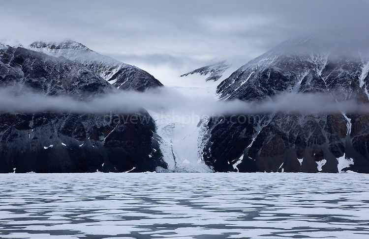 Glacier, sea ice, and low lying cloud in Dijmhna Sund, Nioghalvfjerdsfjorden, Greenland. The mountains of northeast Greenland seen from Dijmhna Sound, near 79 Glacier, at 79 north, from the deck of the Greenpeace ship Arctic Sunrise.