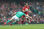 Ireland flanker Sean O'Brien tackles Wales centre Jamie Roberts.<br /> RBS 6 Nations<br /> Wales v Ireland<br /> Millennium Stadium<br /> 14.03.15<br /> &copy;Steve Pope - SPORTINGWALES