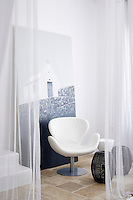A white leather Arne Jacobsen Swan chair in the corner of a room with a floor standing artwork behind.