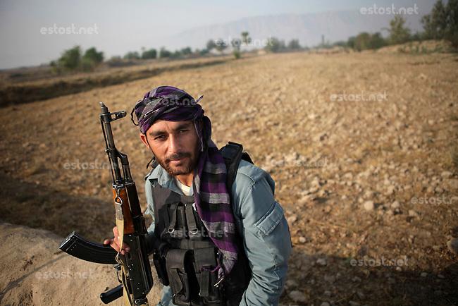 Afghanistan, 26.10.2011, Nawabad. Ein afghanischer Polizist schaut einer ISAF Patrouille zu. Die in Kundus stationierte 3. Task Force (ISAF) der Bundeswehr beginnt im Oktober 2011 die mehrtaegige Operation Orpheus. Durch Patrouillen in und um die Kleinstadt Nawabad (Dirstrikt Chahar Dareh) westlich von Kundus, Nordafghanistan, versuchen die rund 100 Infanteristen Rueckzugsorte Aufstaendischer unmoeglich zu machen. Unterstuetzt werden sie dabei durch einen Zug afghanischer Soldaten. An afghan national policeman sit aside and watches an ISAF patrol. In October 2011 Kunduz based 3.Task Force started a several days operation in and around Nawabad (District Chahar Dareh), west of Kunduz, northern Afghanistan. During the Operation Orpheus about 100 german infantry soldiers went out for patrols through the town and surrounding areas, which were expected as a retreat zone of insurgents. A platoon of afghan soldiers supports the german forces. © Timo Vogt/Est&Ost, NO MODEL RELEASE !!